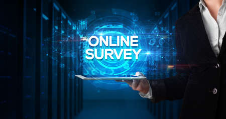 Young business person working on tablet and shows the inscription: ONLINE SURVEY, business concept