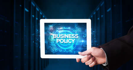 Young business person working on tablet and shows the inscription: BUSINESS POLICY, business concept
