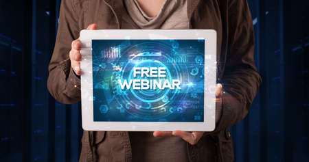 Young business person working on tablet and shows the inscription: FREE WEBINAR, business concept