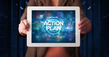 Young business person working on tablet and shows the inscription: ACTION PLAN, business concept Stock fotó