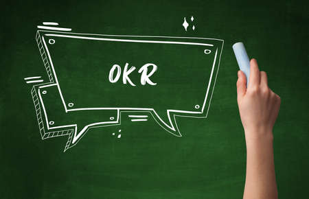 Hand drawing OKR abbreviation with white chalk on blackboard