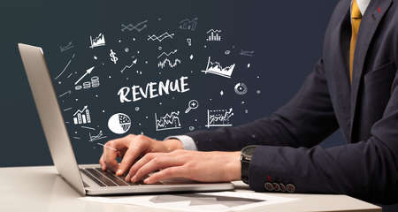 Businessman working on laptop with REVENUE inscription, modern business concept