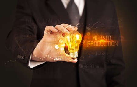 Businessman holding lightbulb with WEBSITE PRODUCTION inscription, Business technology concept