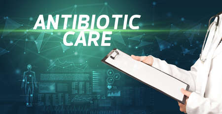 doctor writes notes on the clipboard with ANTIBIOTIC CARE inscription, medical diagnosis concept