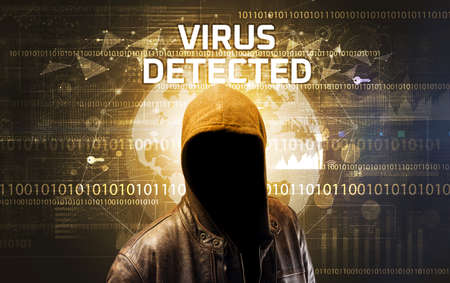 Faceless hacker at work with VIRUS DETECTED inscription, Computer security concept