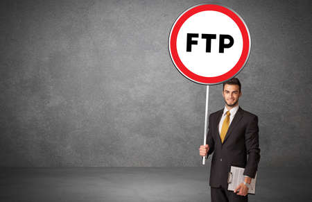 Young business person holdig traffic sign with FTP abbreviation, technology solution concept