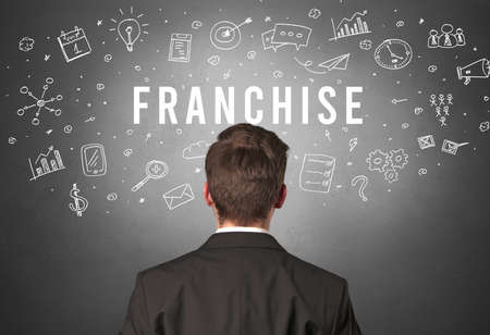 Rear view of a businessman with FRANCHISE inscription, modern business concept