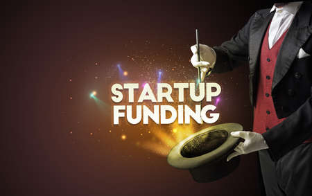 Illusionist is showing magic trick with STARTUP FUNDING inscription, new business model concept