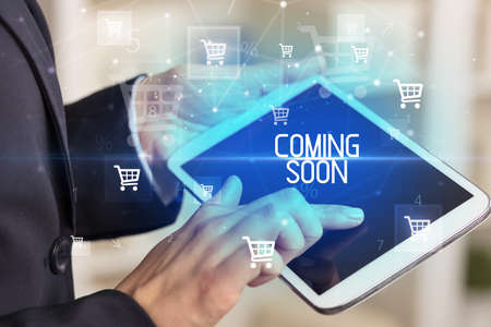Young person makes a purchase through online shopping application with COMING SOON inscription