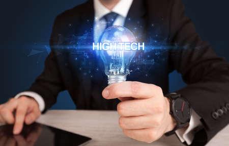 Businessman holding light bulb with HIGH-TECH inscription, innovative technology concept