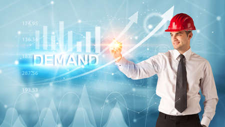 Young businessman with helmet drawing DEMAND inscription, modern business technology concept Stock Photo