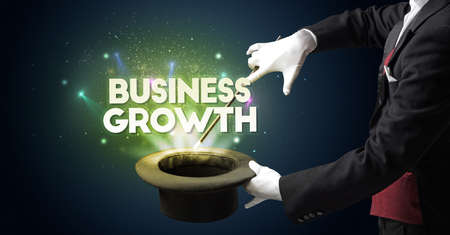 Illusionist is showing magic trick with BUSINESS GROWTH inscription, new business model concept