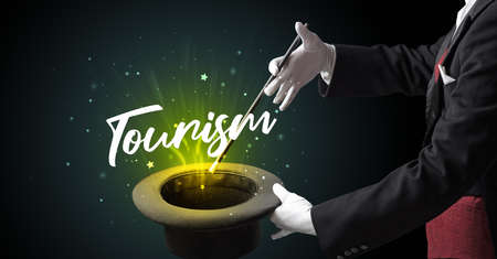 Magician is showing magic trick with Tourism inscription, traveling concept