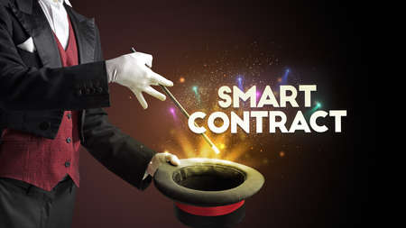 Illusionist is showing magic trick with SMART CONTRACT inscription, new business model concept Фото со стока