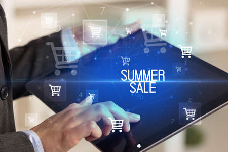 Young person makes a purchase through online shopping application with SUMMER SALE inscription