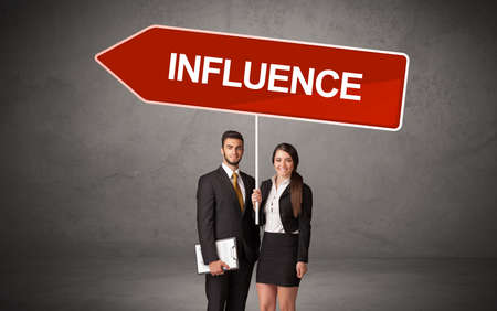 Young business person in casual holding road sign with INFLUENCE inscription, new business direction concept Imagens