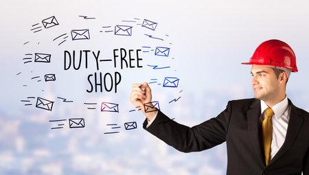 Handsome businessman with helmet drawing DUTY-FREE SHOP inscription, contruction sale concept 写真素材