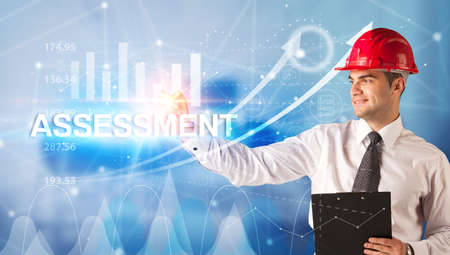Young businessman with helmet drawing ASSESSMENT inscription, modern business technology concept