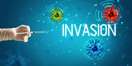Syringe, medical injection in hand with INVASION inscription, coronavirus vaccine concept