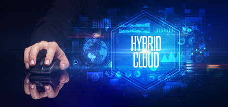 hand holding wireless peripheral with HYBRID CLOUD inscription, cyber security concept