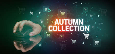 hand holding wireless peripheral with AUTUMN COLLECTION inscription, online shopping concept
