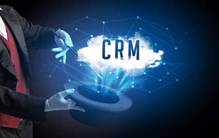 Magician is showing magic trick with CRM abbreviation, modern tech concept