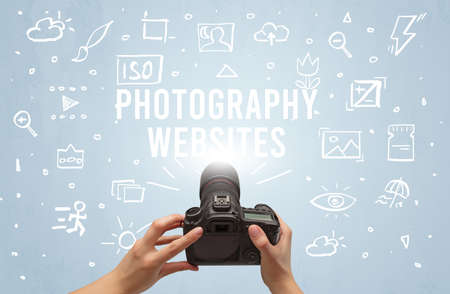 Hand taking picture with digital camera and PHOTOGRAPHY WEBSITES inscription, camera settings concept