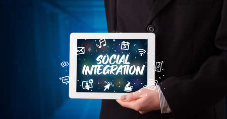 Young business person working on tablet and shows the inscription: SOCIAL INTEGRATION Stockfoto