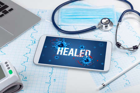 Tablet pc and doctor tools on white surface with HEALED inscription, pandemic concept Imagens