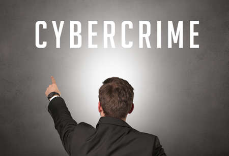 Rear view of a businessman with CYBERCRIME inscription, cyber security concept