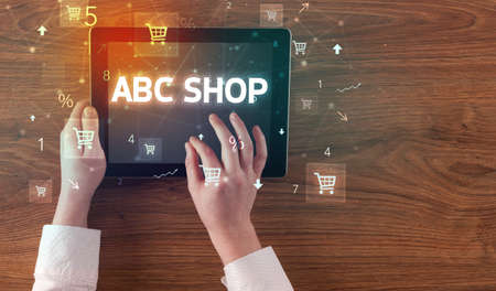 Close-up of a hand holding tablet with ABC SHOP inscription, online shopping concept