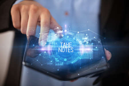 Young man holding a foldable smartphone with TAKE NOTES inscription, educational concept