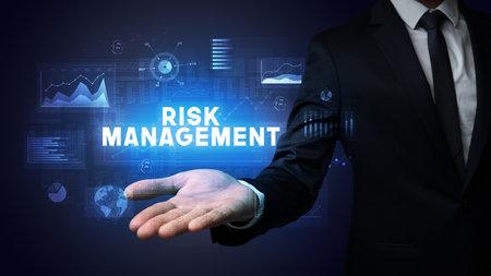 Hand of Businessman holding RISK MANAGEMENT inscription, business success concept
