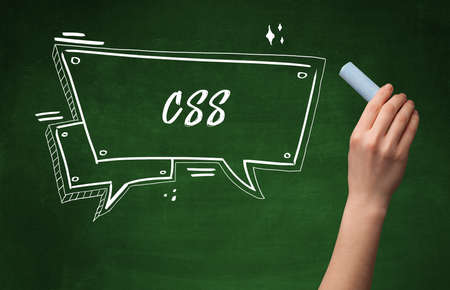 Hand drawing CSS abbreviation with white chalk on blackboard