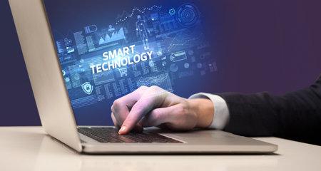 Businessman working on laptop with SMART TECHNOLOGY inscription, cyber technology concept Zdjęcie Seryjne