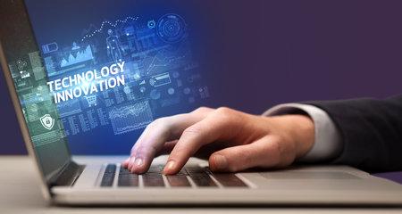 Businessman working on laptop with TECHNOLOGY INNOVATION inscription, cyber technology concept Zdjęcie Seryjne