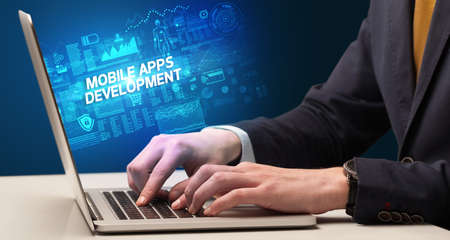 Businessman working on laptop with MOBILE APPS DEVELOPMENT inscription, cyber technology concept
