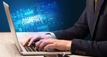 Businessman working on laptop with BACKWARD COMPATIBLE inscription, cyber technology concept