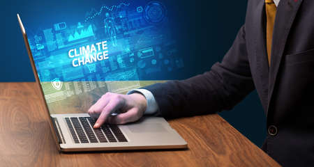 Businessman working on laptop with CLIMATE CHANGE inscription, cyber technology concept