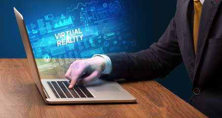Businessman working on laptop with VIRTUAL REALITY inscription, cyber technology concept