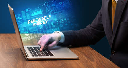 Businessman working on laptop with RENEWABLE ENERGY inscription, cyber technology concept