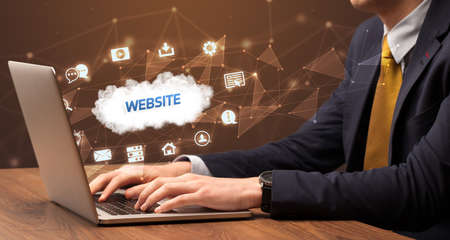 Businessman working on laptop with WEBSITE inscription, modern technology concept