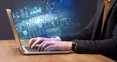 Businessman working on laptop with ASSISTIVE TECHNOLOGY inscription, cyber technology concept