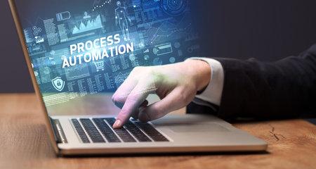 Businessman working on laptop with PROCESS AUTOMATION inscription, cyber technology concept Zdjęcie Seryjne