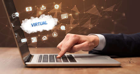 Businessman working on laptop with VIRTUAL inscription, modern technology concept