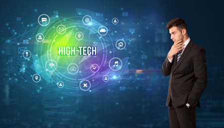 Businessman thinking in front of technology related icons and HIGH-TECH inscription, modern technology concept