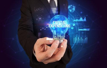 Businessman holding lightbulb with CAPITAL EXPENDITURE inscription, Business idea concept