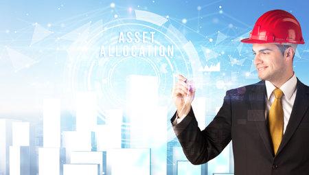 Handsome businessman with helmet drawing ASSET ALLOCATION inscription, contruction business concept