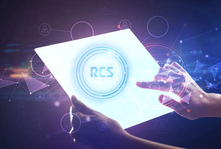 Hand holdig futuristic tablet with RCS inscription, modern technology concept