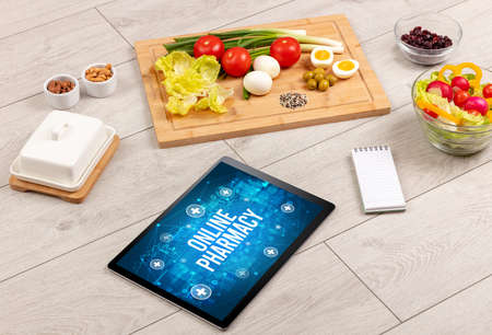 ONLINE PHARMACY concept in tablet pc with healthy food around, top view